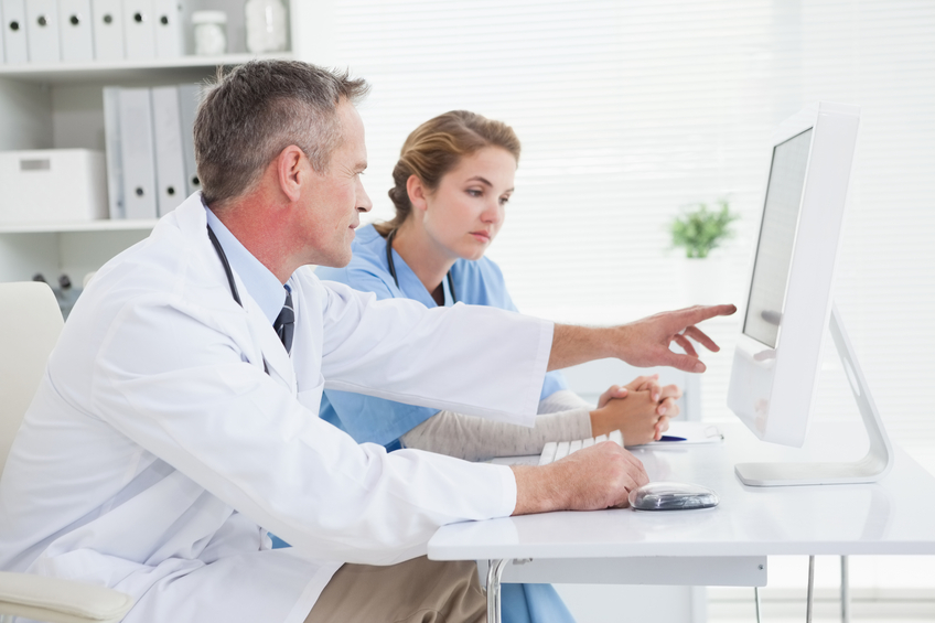 A doctor and a nurse looking at simulations on a computer.