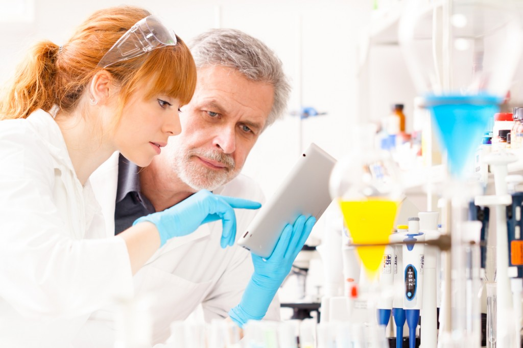 A young female scientist and her senior male supervisor looking at the results from a preclinical trial.